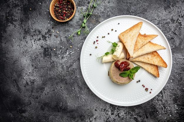 Patê de fígado de frango caseiro fresco com manteiga, tomates secos ao sol e pão