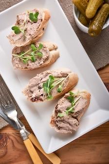 Patê de fígado de galinha com sanduíches de pão de porto geléia e picled cucambres.