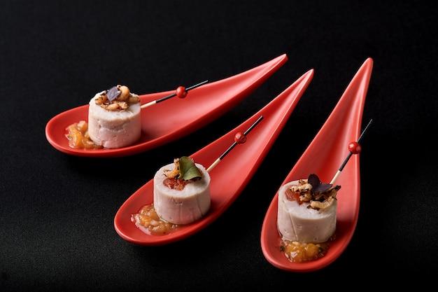 Patê de fígado de ganso, foie gras, servido em pedra preta em colheres vermelhas japonesas. pasta servida com geléia e nozes. fusão conceito de comida, chave baixa, copie o espaço.
