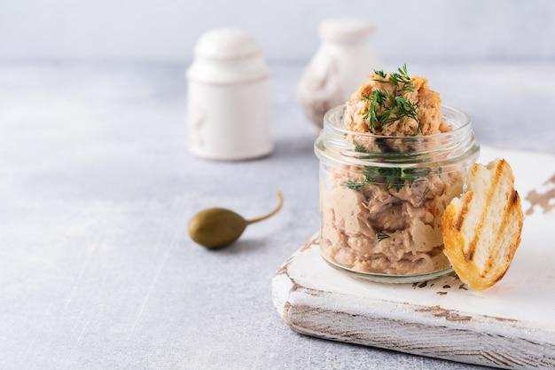 Patê de pasta de carne de frango em uma jarra servida com alcaparras sobre um concreto leve.
