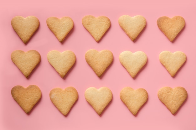 Patern de biscoitos caseiros em forma de coração em rosa. postura plana.