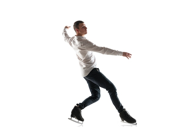 Patinação artística do homem isolada na parede branca do estúdio com copyspace. prática profissional e treinamento em ação e movimento no gelo. gracioso e sem peso. conceito de movimento, esporte, beleza.