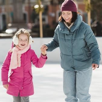 Patinação no gelo feliz menina e mãe