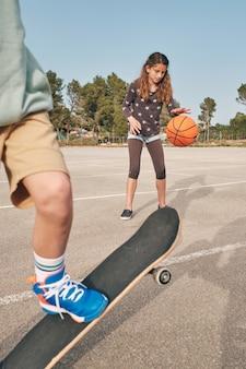 Patinador adolescente e menina com bola de basquete se exercitando juntos