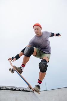 Patinador maduro e confiante com um boné de relógio, começando a rolar em uma pista de skate. ângulo para cima, inclinado para o lado, inclinado para a frente.
