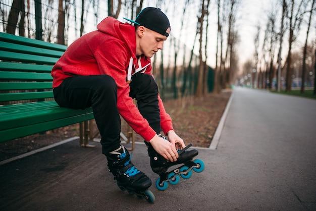 Patinador sentado no banco e amarrando os patins
