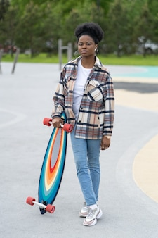 Patinadora africana segurando longboard no skate park feminino urbano com roupas casuais no skatepark