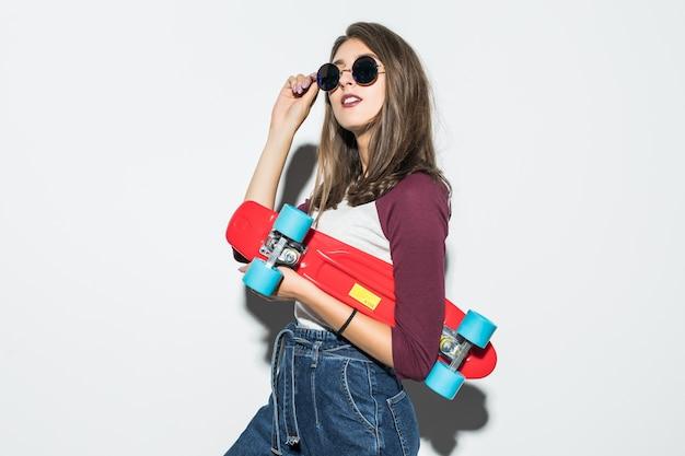 Patinadora bonita com roupas casuais e óculos escuros segurando um skate vermelho