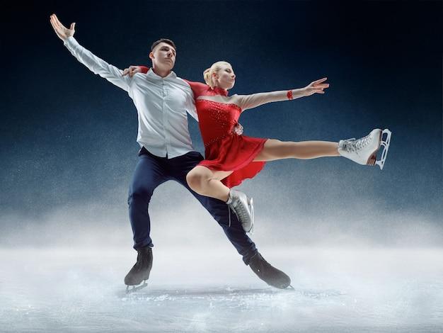 Patinadores profissionais masculinos e femininos realizando show ou competição na arena de gelo