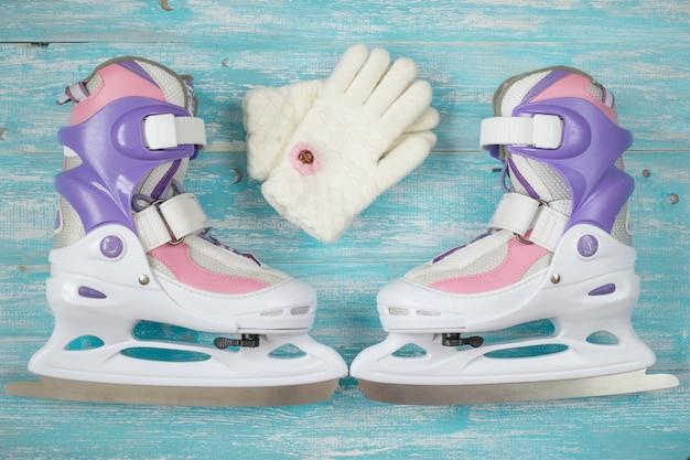 Patins de gelo para crianças com tamanho ajustável e acessórios no piso de madeira.