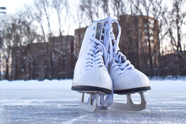 Patins femininos brancos ficam no gelo. pista de patinação no gelo de entretenimento de inverno.