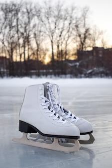 Patins femininos brancos ficam no gelo. vista do topo. pista de patinação no gelo de entretenimento de inverno.