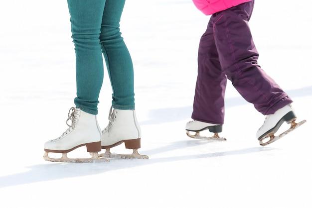 Patins infantis e adultos na pista de gelo. esporte e entretenimento. descanso e férias de inverno.