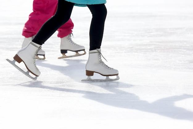 Patins infantis e adultos na pista de gelo