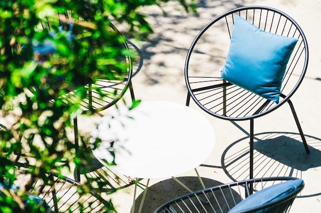 Pátio com travesseiro na cadeira e conjunto de mesa