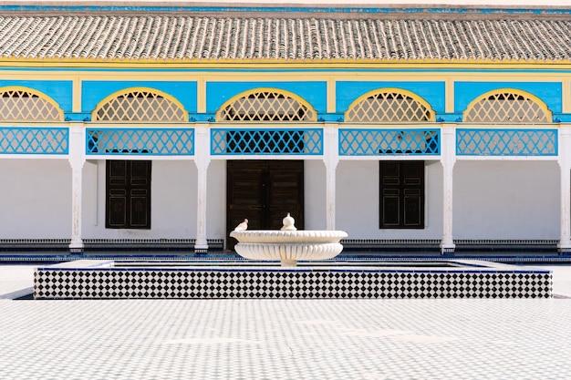 Pátio interno cercado por colunas com arcos coloridos com mosaicos no chão e uma fonte