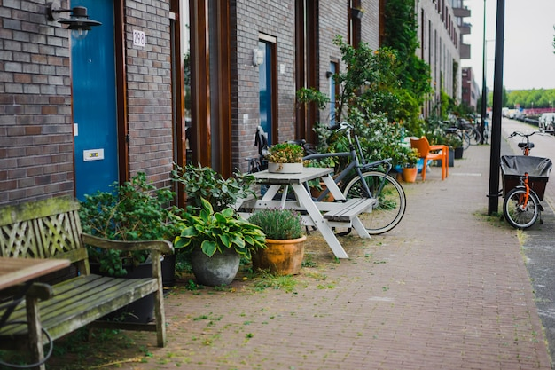 Pátios aconchegantes de amsterdã, bancos, bicicletas, flores em banheiras.