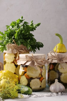 Patissons caseiros em conserva, pepinos com cenoura e alho em potes de vidro e ingredientes frescos em um cinza claro