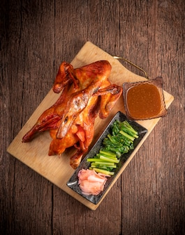 Pato assado com molho e legumes servido em uma velha mesa de madeira