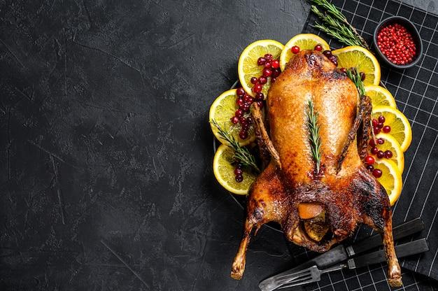 Pato assado recheado com laranjas e alecrim. fundo de mesa festiva