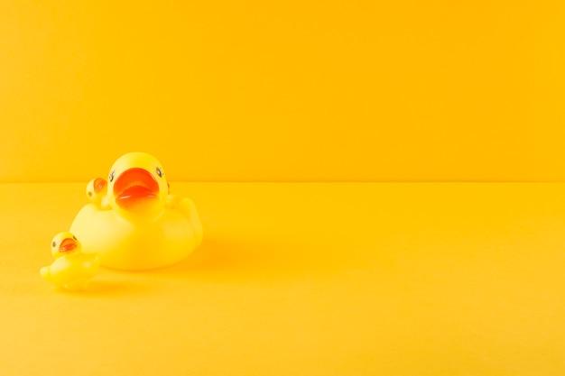 Pato de borracha e patinhos em pano de fundo amarelo