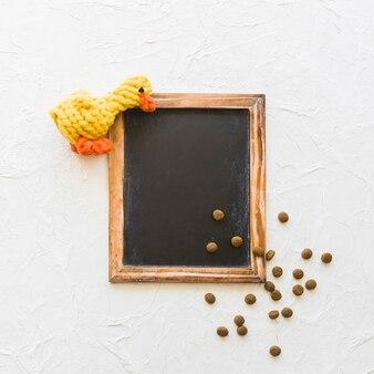 Pato de brinquedo e pet food perto de quadro-negro