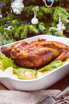 Pato de natal com maçãs e ervas em uma panela branca com decorações de férias de inverno