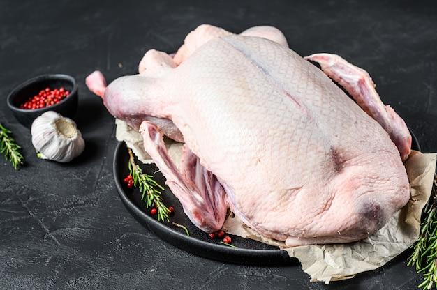 Pato inteiro cru, pimenta rosa e alecrim.