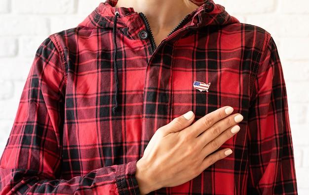 Patriotismo, conceito de votação. mulher com sinal de bandeira dos eua colocando a mão no coração