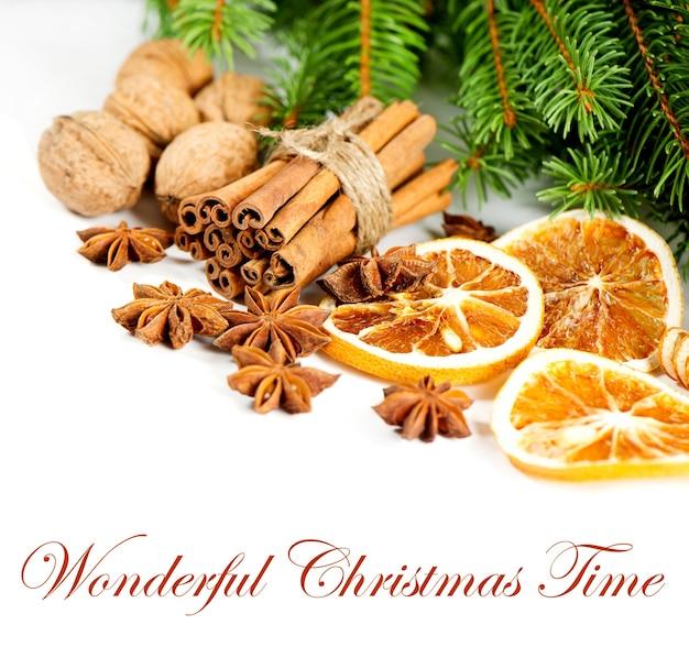 Paus de canela, anis estrelado e rodelas de laranja seca com brunch de pinho. decoração de natal. exemplo de texto - tempo maravilhoso de natal