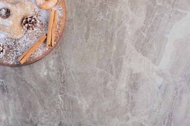 Paus de canela, biscoitos e pinhas adornando um bolo revestido de pó de baunilha sobre mármore.