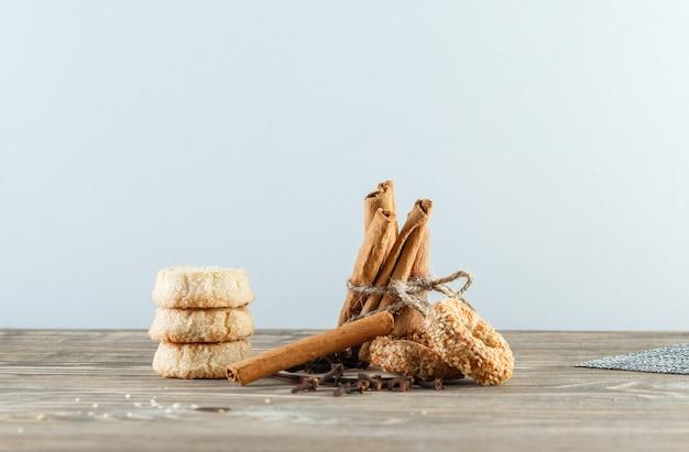 Paus de canela com biscoitos, cravo, placemat na parede de madeira e branca, vista lateral.