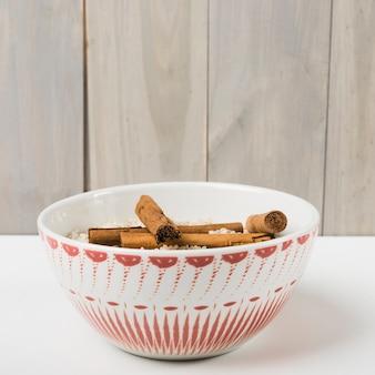 Paus de canela com tigela de arroz cru na mesa contra fundo de madeira