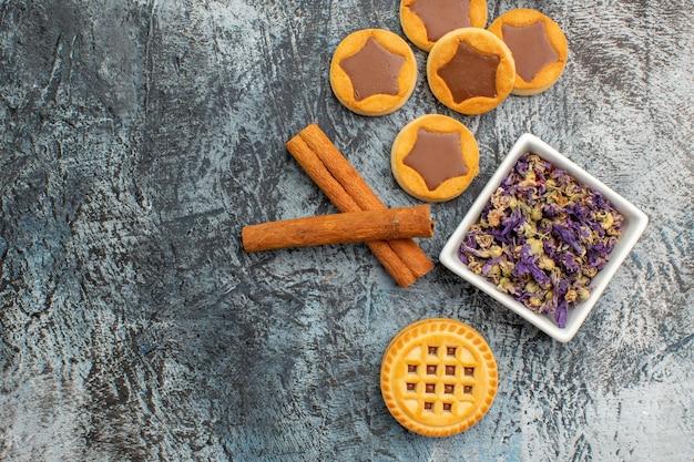 Paus de canela com uma tigela de flores secas e biscoitos em cinza