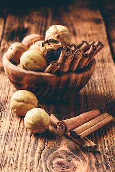 Paus de canela e limas secas em uma tigela de madeira na mesa rústica