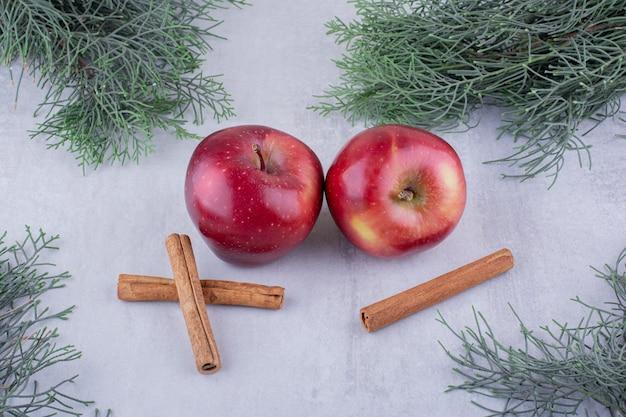 Paus de canela e maçãs agrupam-se entre ramos de pinheiro em fundo branco.