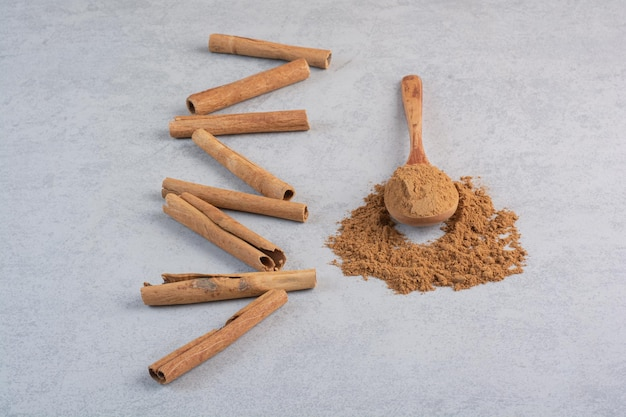 Paus de canela e pó misturado em uma colher de pau.