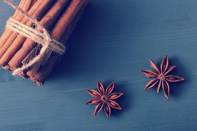Paus de canela e sementes de anis em um fundo escuro de madeira rústico