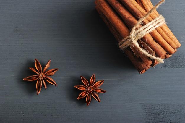 Paus de canela e sementes de anis em uma superfície de madeira rústica escura
