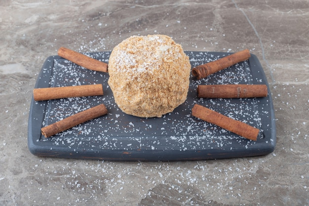 Paus de canela e um bolo de esquilo em uma placa na superfície de mármore