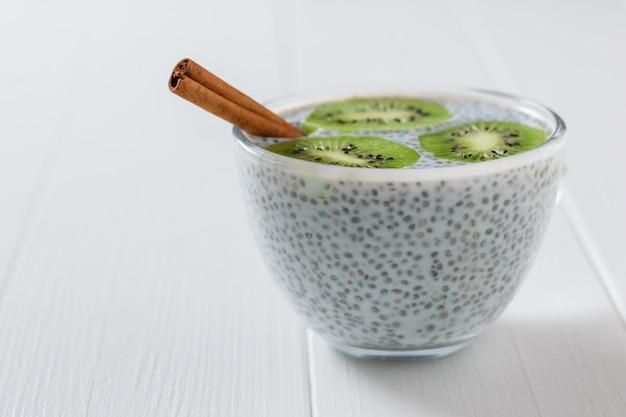 Paus de canela e uma tigela de vidro de sementes de chia com leite na mesa branca.