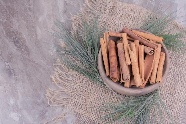 Paus de canela em um copo de madeira com um galho de carvalho ao redor
