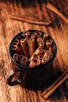 Paus de canela em uma caneca de metal em uma superfície de madeira rústica