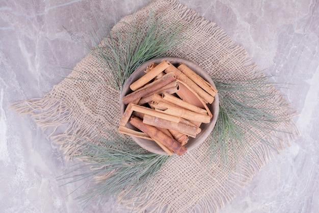 Paus de canela em uma xícara de madeira com galhos de carvalho ao redor.