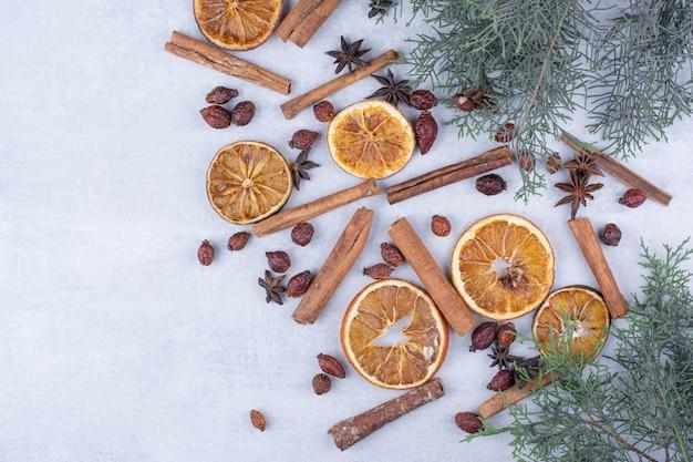 Paus de canela, frutos de rosa e rodelas de laranja secas na superfície.