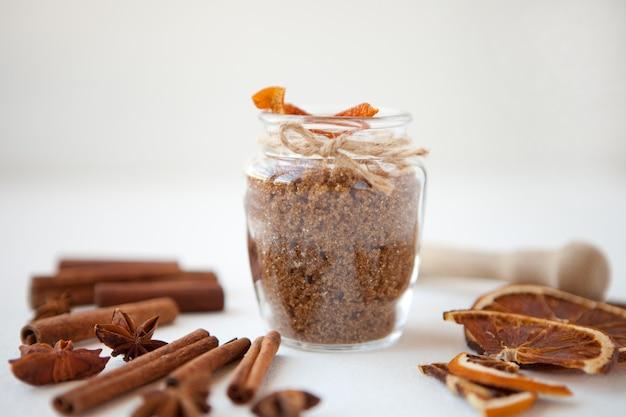 Paus de canela, laranjas secas e anis estrelado com garrafa de açúcar mascavo em profundidade de campo