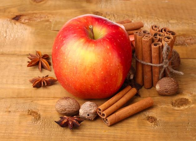 Paus de canela, maçã vermelha, noz-moscada e anis na mesa de madeira