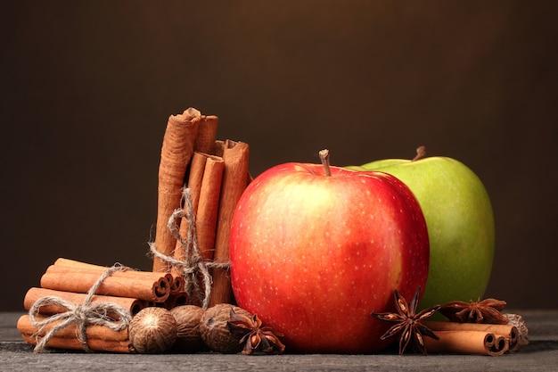 Paus de canela, maçãs, noz-moscada e anis na mesa de madeira no fundo marrom