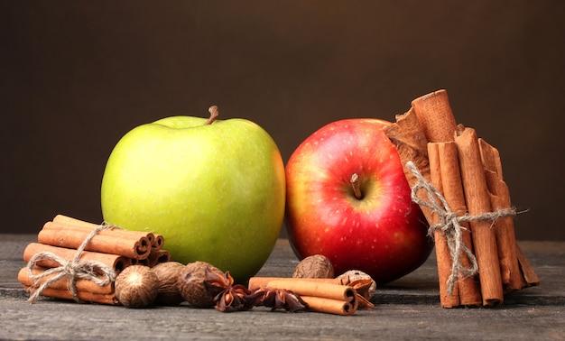 Paus de canela, maçãs, noz-moscada e anis na mesa de madeira no marrom