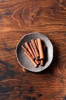 Paus de canela naturais em uma mesa rústica de marrom. especiarias naturais.